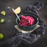 Bowl of pickled red onions with spoon
