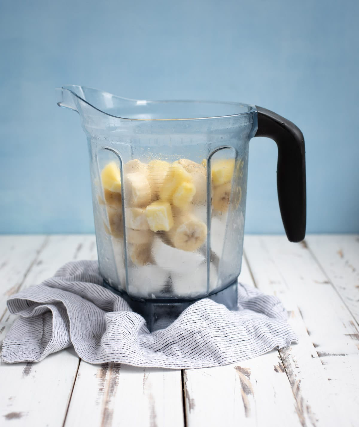 blender pitcher with banana ice cream ingredients before being blended