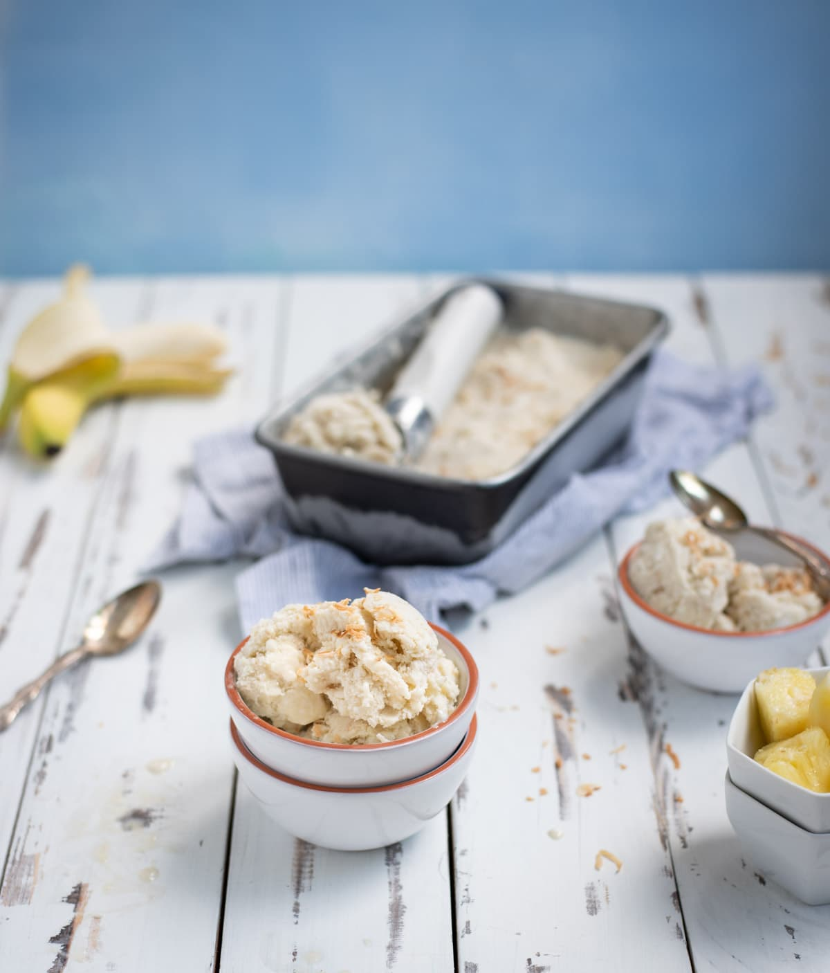 two bowls of banana ice cream with bananas and tin of ice cream