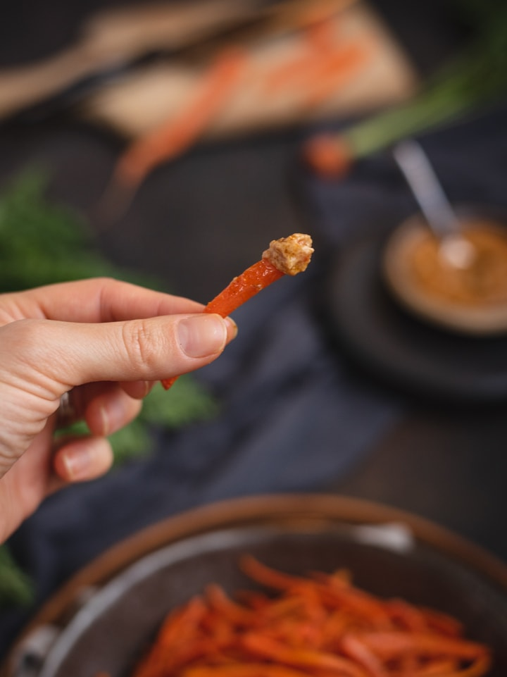 hand holding carrot fry that was dipped in sauce