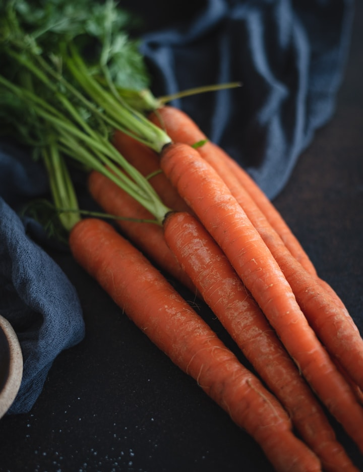 pile of carrots on dark background