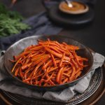 bowl of carrot fries on dark background
