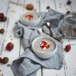 Picture of almond chia seed pudding on a table with strawberries