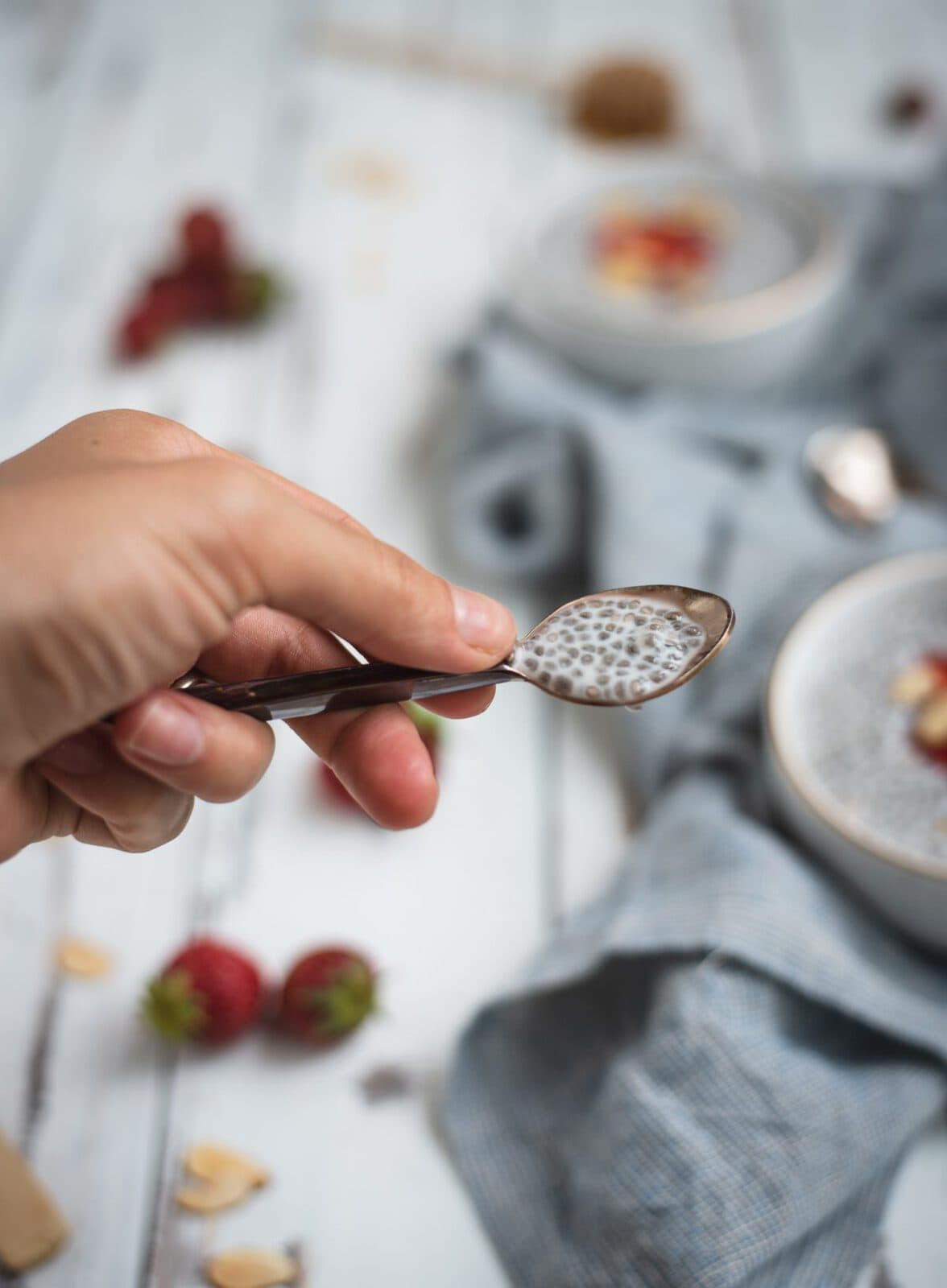 Almond chia seed pudding on a spoon held up by a hand