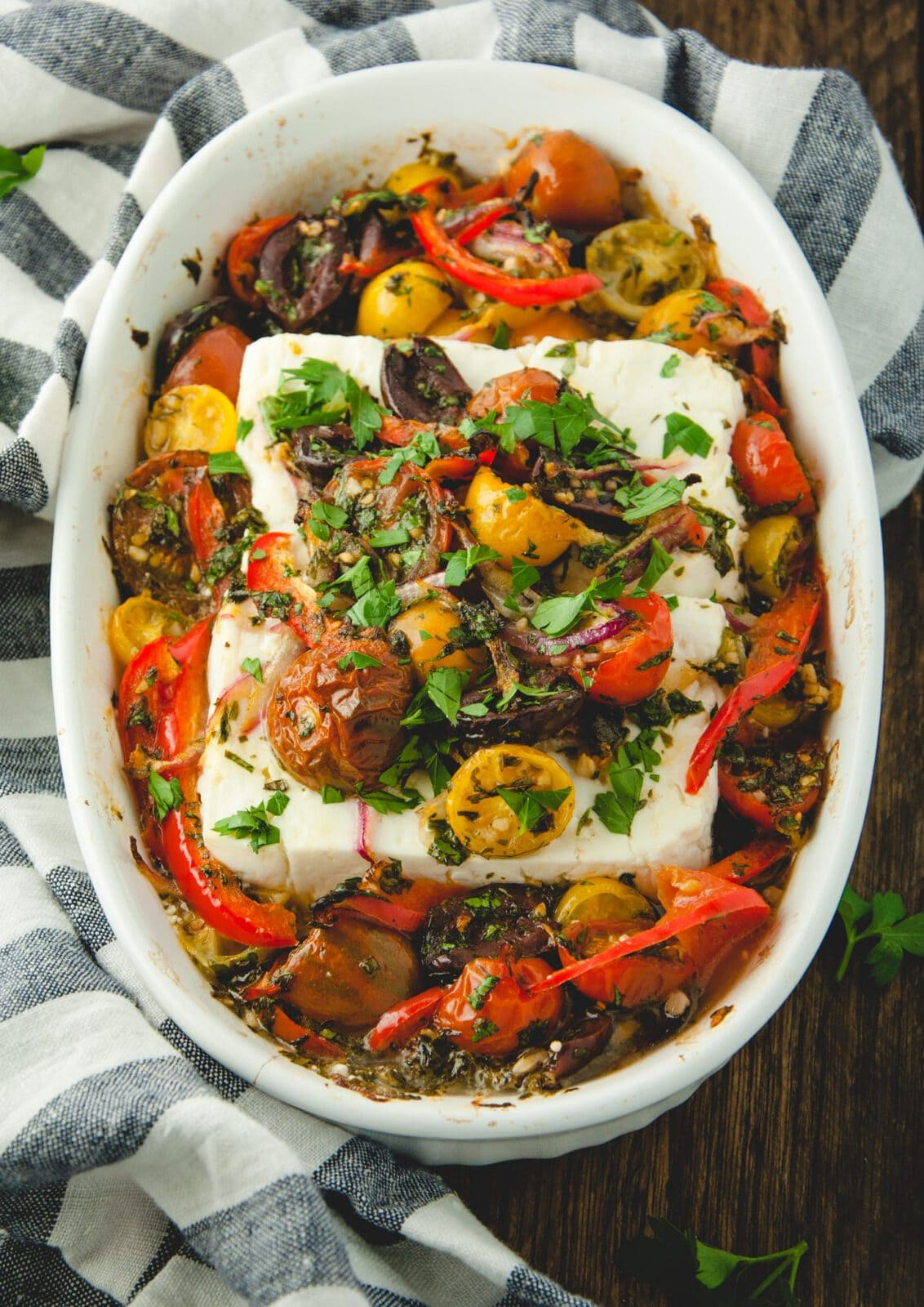 White dish with baked feta topped with tomatoes, herbs, olives and peppers