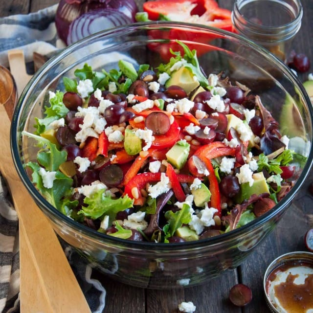 Close up picture of green salad with grapes and feta and curry balsamic dressing