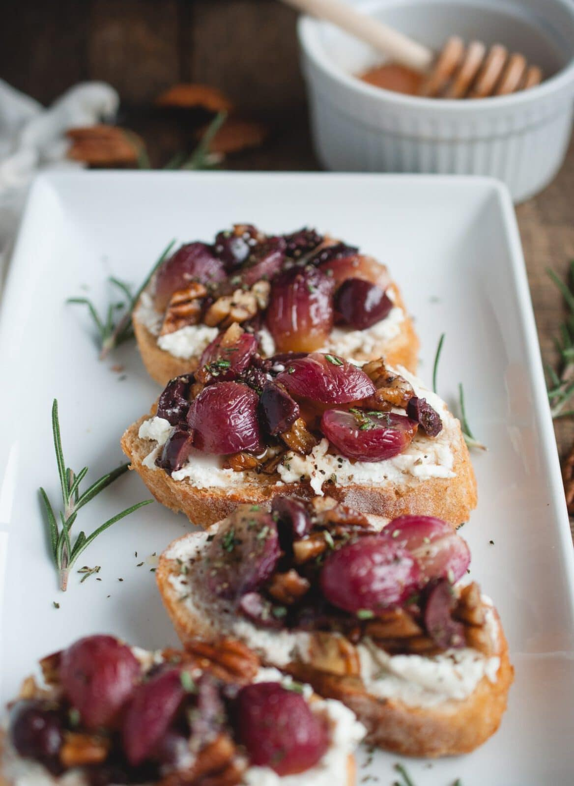 close up picture of plate with four pieces of appetizer Crostini with Roasted Grapes