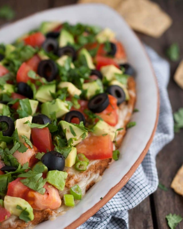 This Mexican bean dip is easy and tasty as can be with Greek yogurt adding a nutrition and protein punch. The melted cheese and toppings take it over the top!