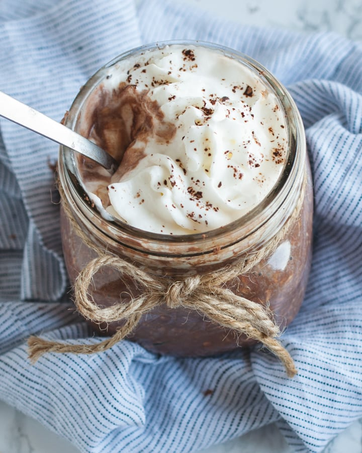 close up overhead picture of chocolate overnight oats with whipped cream on top