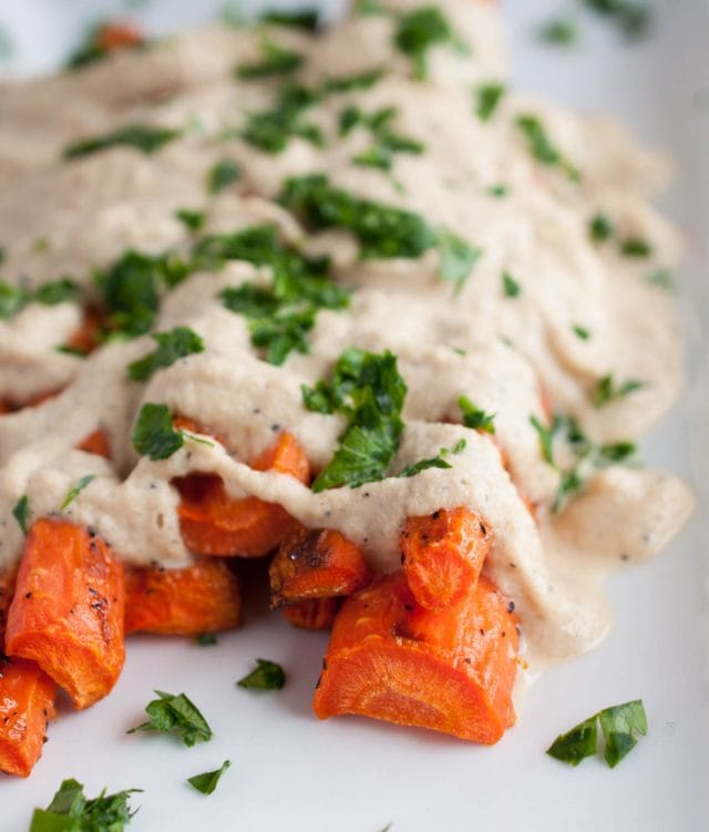 Cashew cream sauce is drizzled over perfectly roasted caramelized carrots in this easy, flavorful, absolutely delicious, naturally vegan dish.