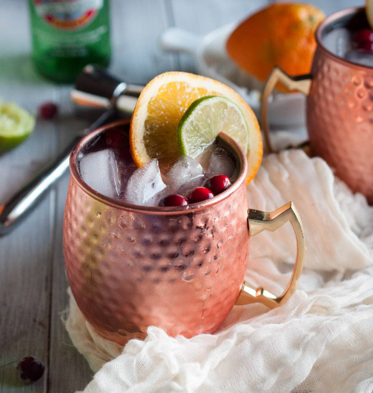 Cranberry Moscow mule recipe made with zesty orange, zippy ginger beer, vodka, lime, and cranberry just might be the most refreshing drink on the planet. Try one today!