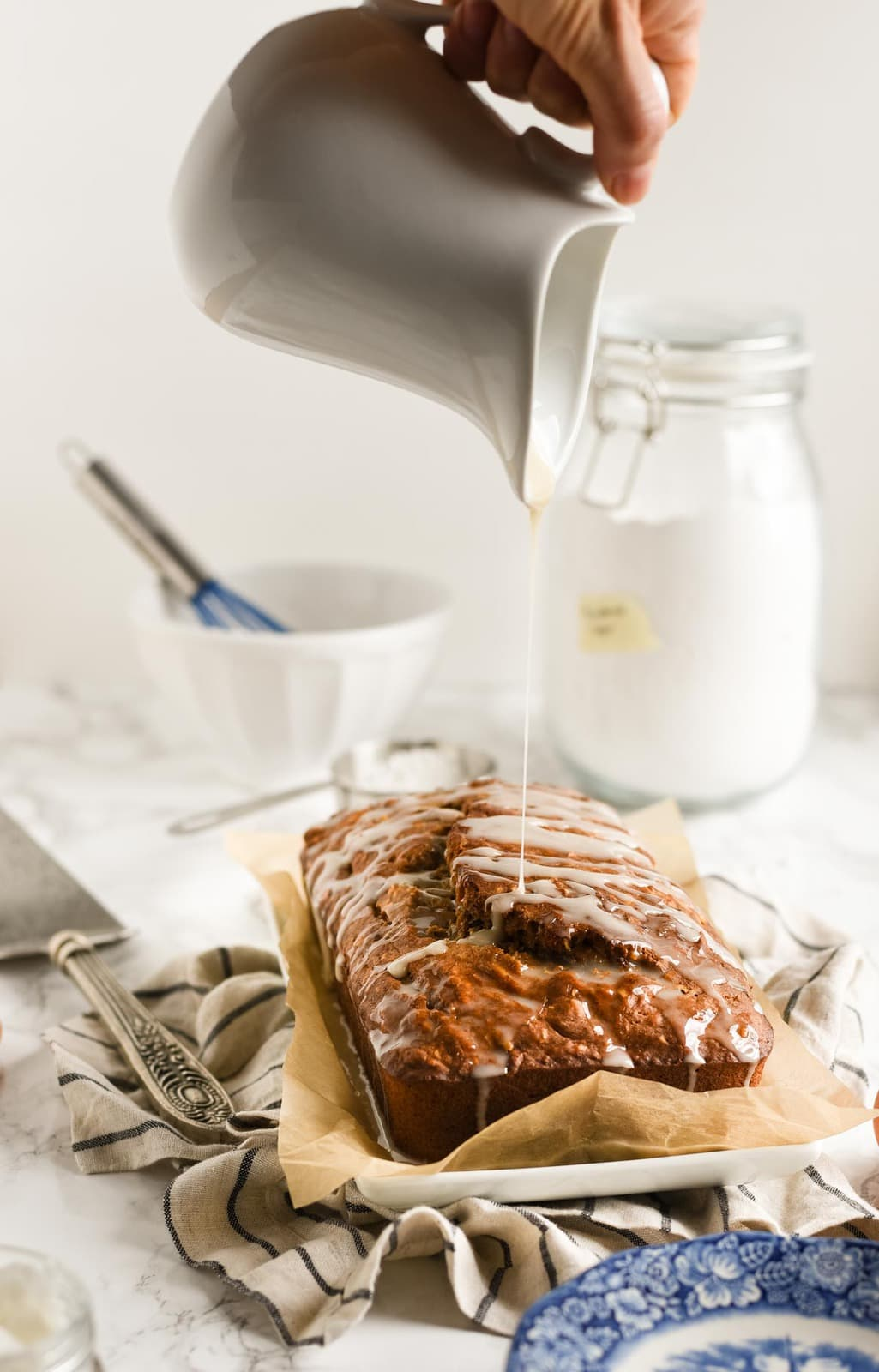 banana bread with glaze being drizzled on top