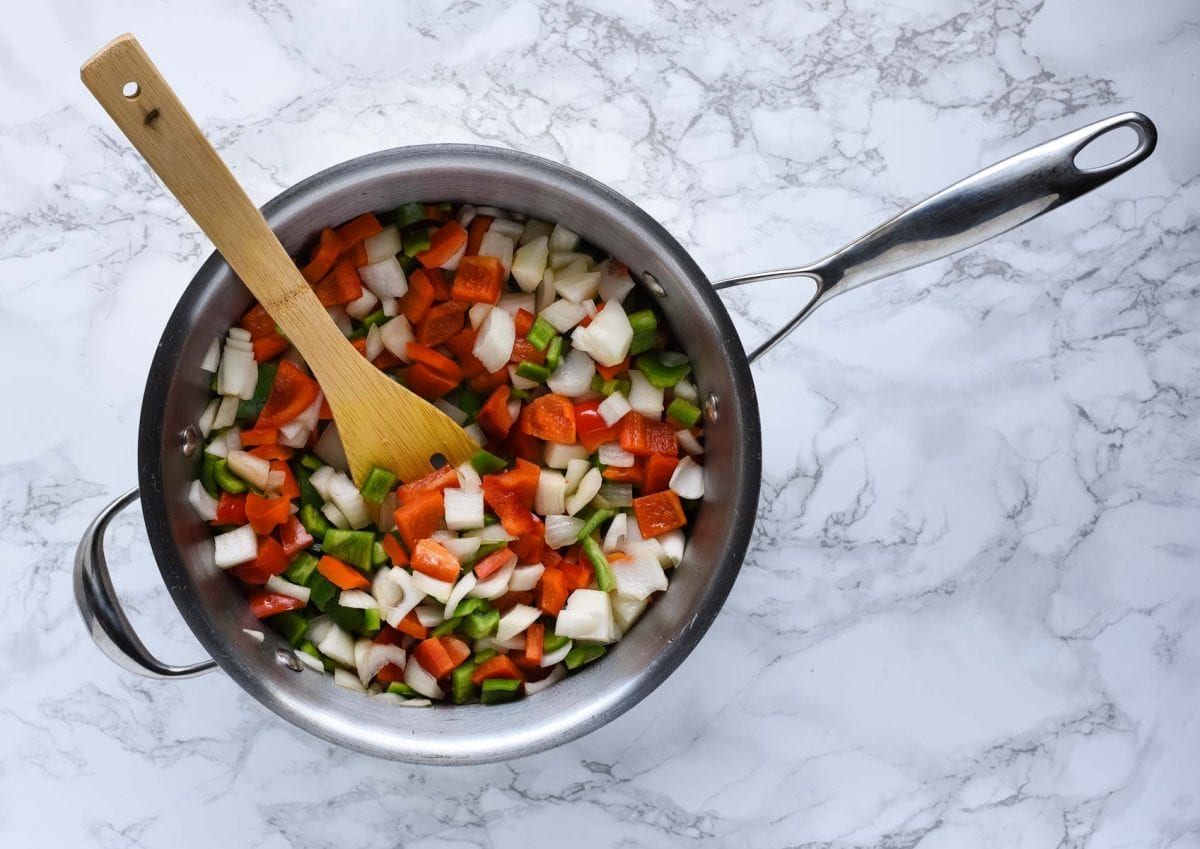 chopped green pepper, red pepper, and onion in a pan with a wooden spoon