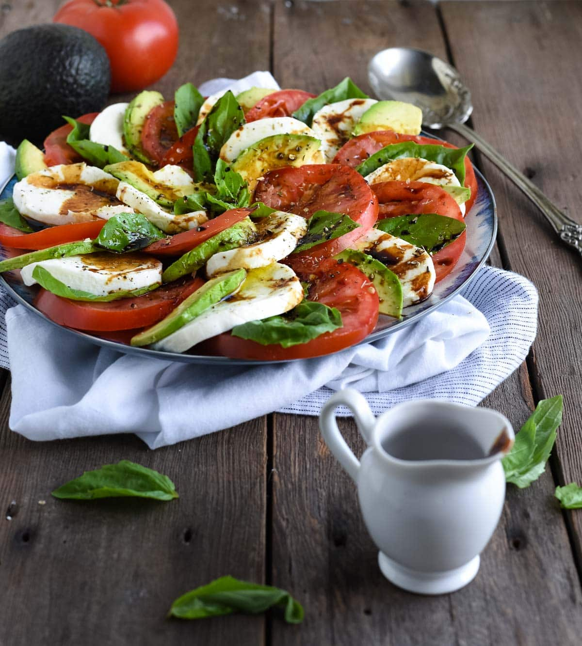 avocado caprese salad shot on wood backdrop