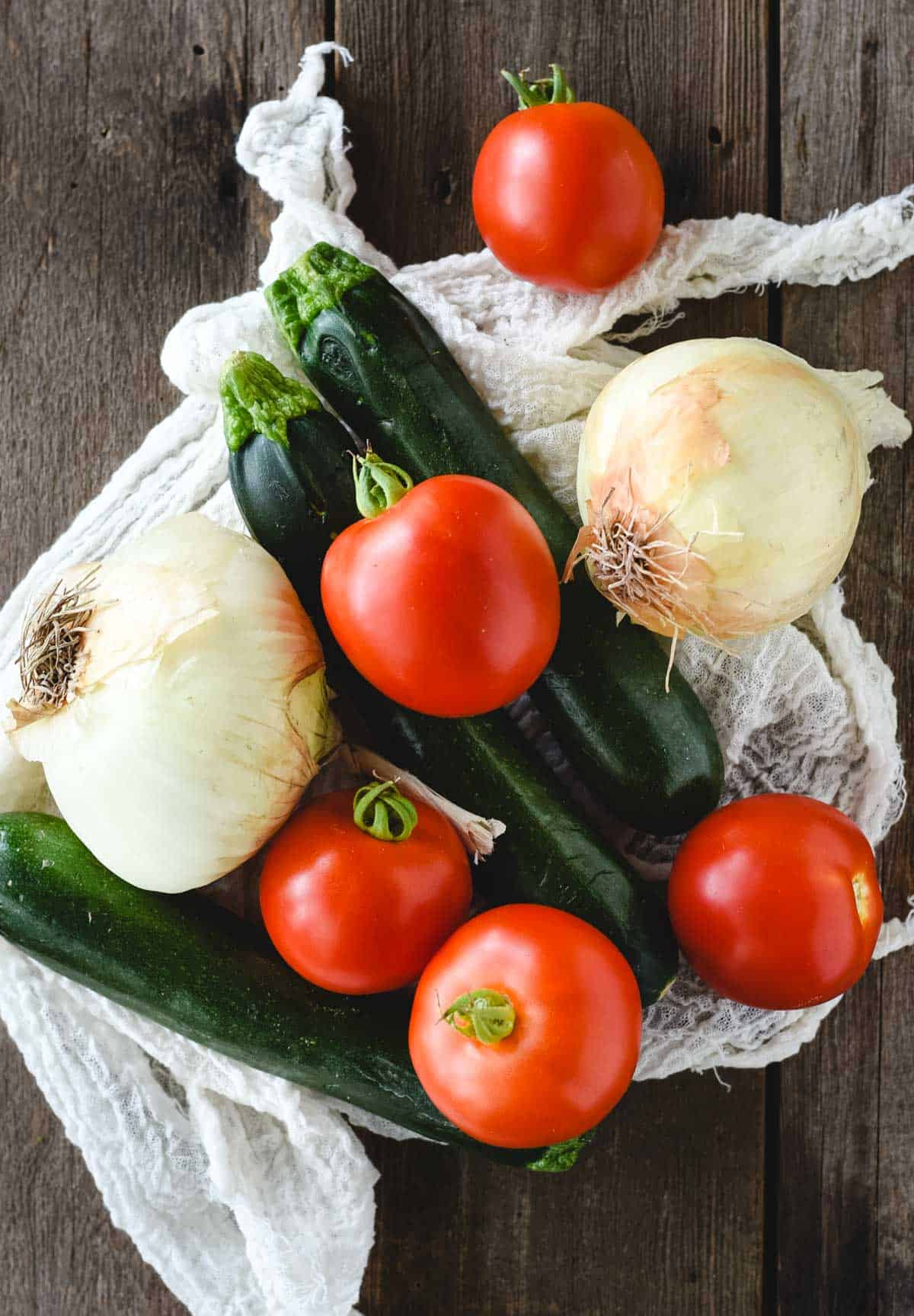 overhead picture of onions, tomatoes, and zucchini on a dark wood background