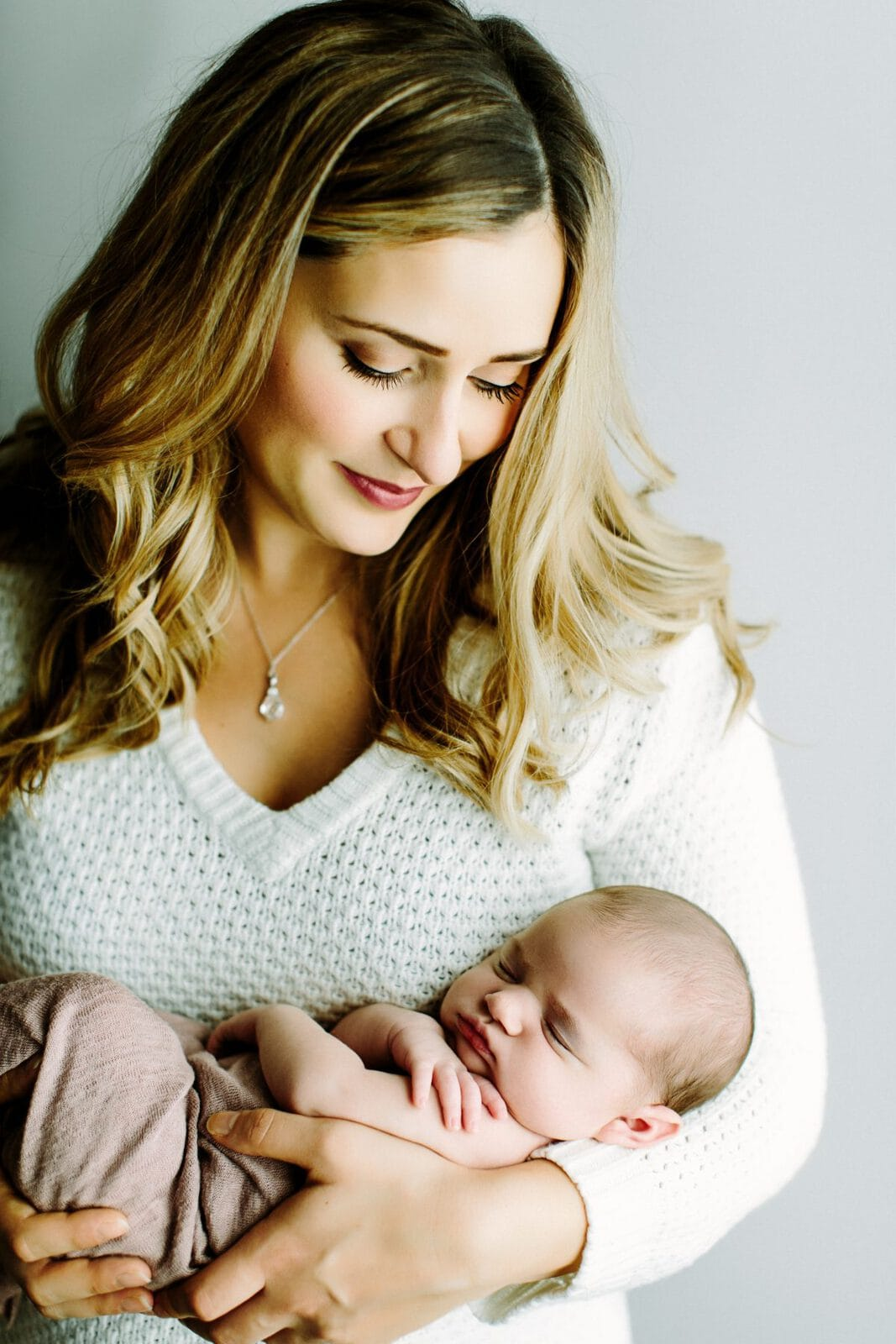 mother holding newborn baby girl in arms