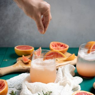 Hand sprinkling salt in Rosemary grapefruit mocktail