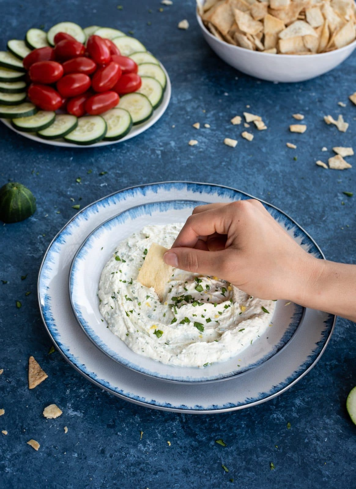 Hand with chip scooping whipped feta with herbs