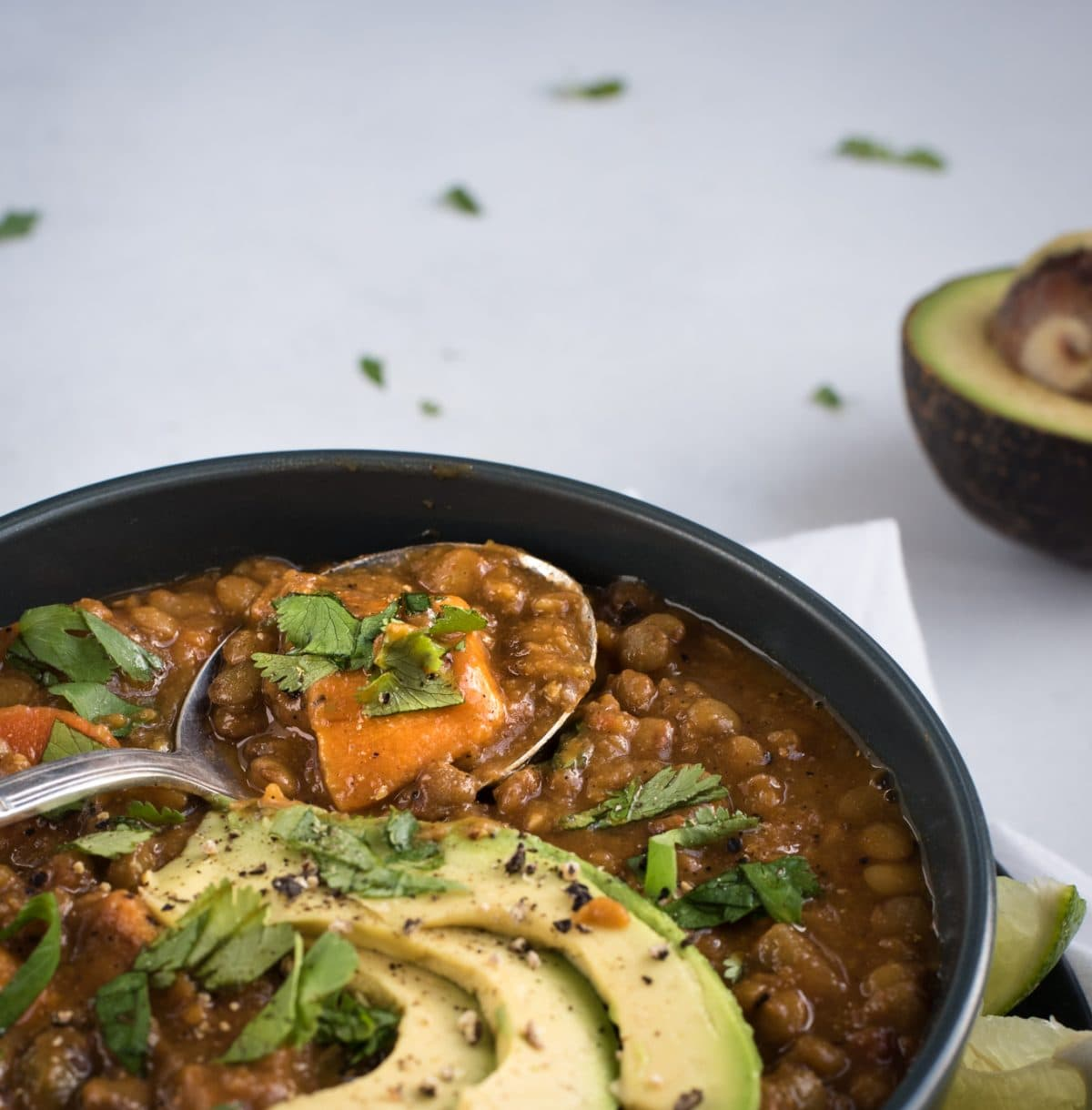 Spoon full of sweet potato lentil soup in a bowl