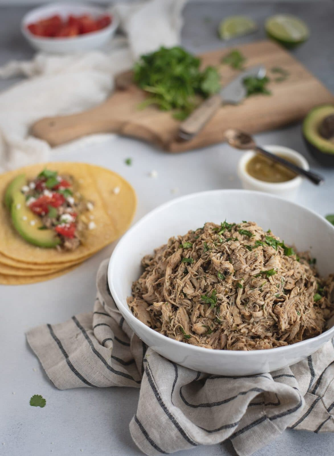 bowl of slow cooker cilantro lime chicken with corn taco in background