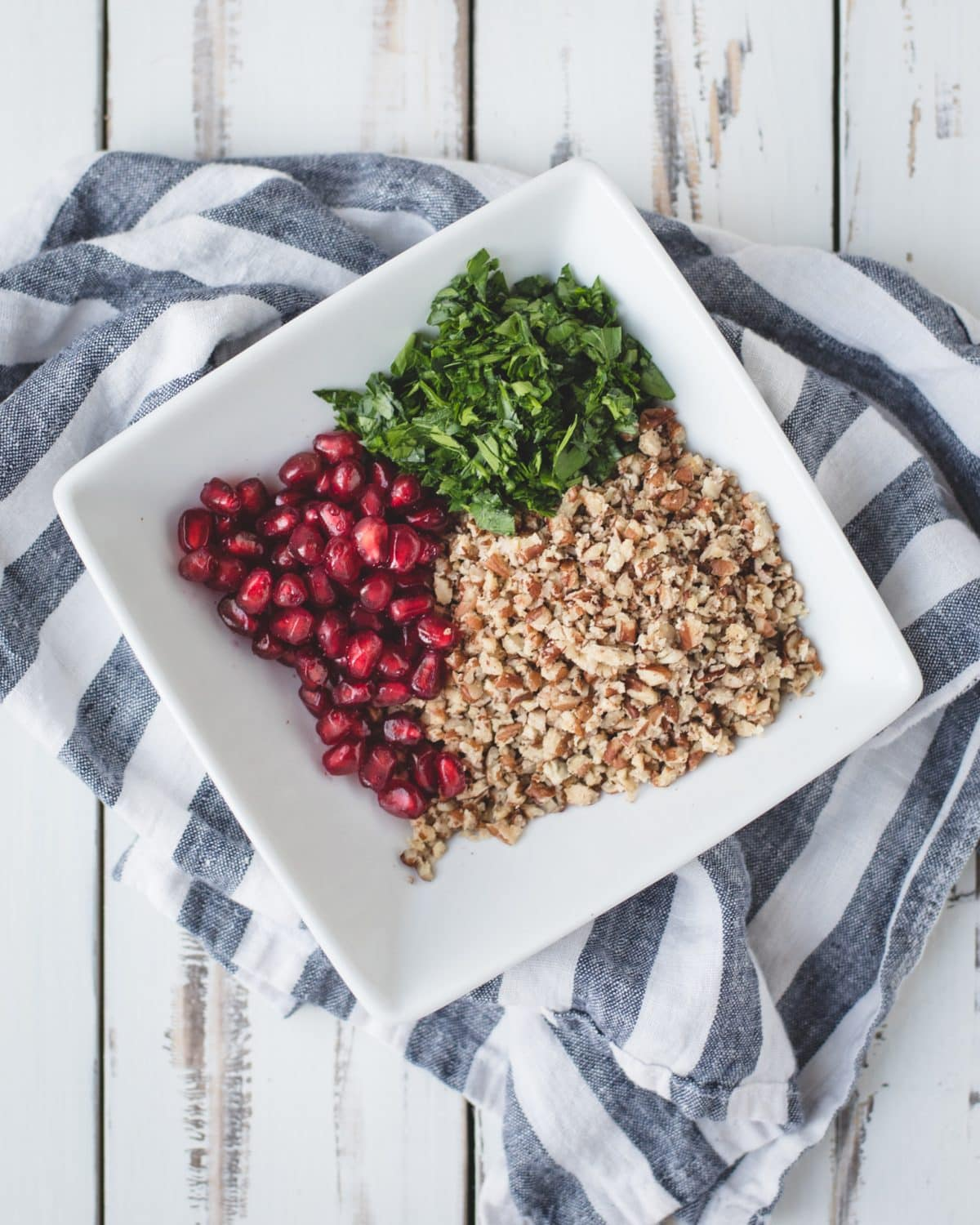 pomegranate, parsley, and crushed pecans in a white bowl