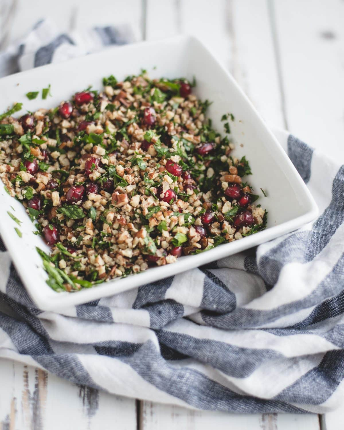 Tossed pomegranate, parsley, and crushed pecans in a bowl