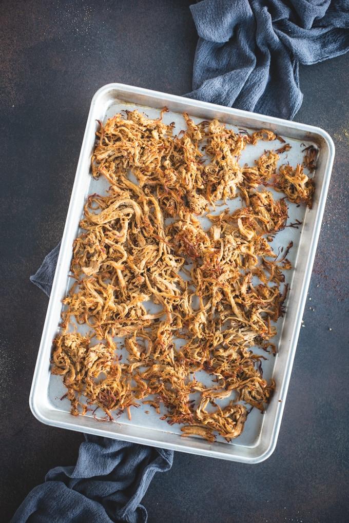 Overhead photo of shredded pork tenderloin carnitas on a silver pan