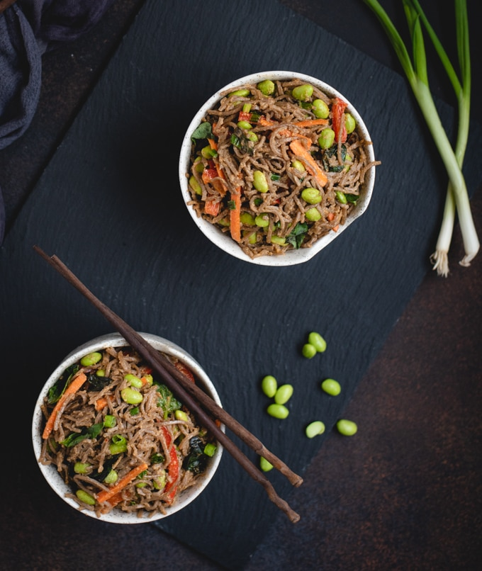 overhead picture of two bowls of soba noodles tossed with vegetables in peanut sauce
