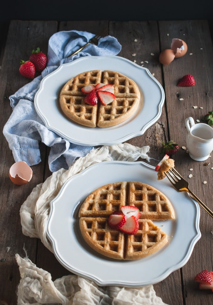 wood table with two white plates with waffles on them, topped with strawberries