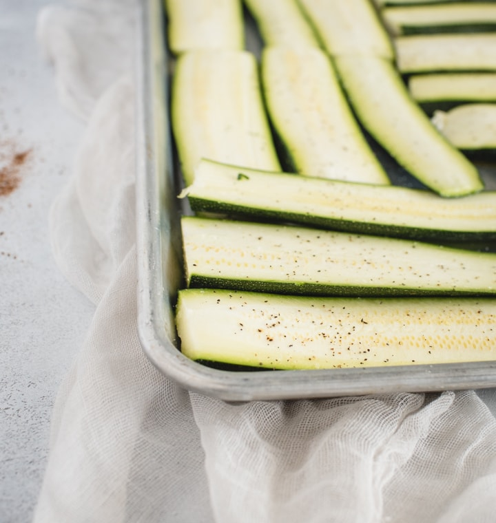 baking sheet with sliced zucchini laid out on it
