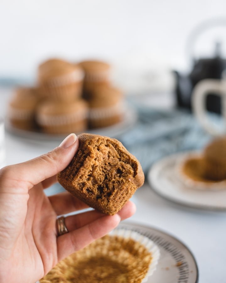 Hand holding healthy pumpkin muffin with bite taken out of it