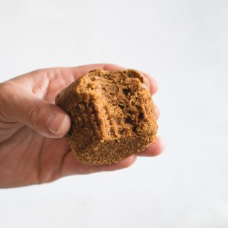 Close up picture of hand holding pumpkin muffin against white background