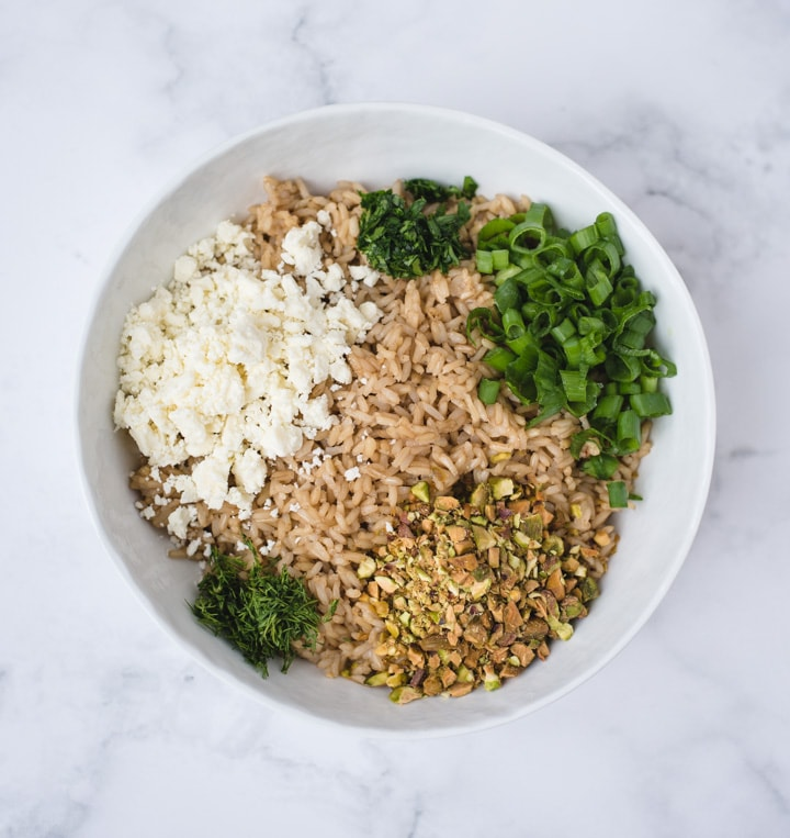 Bowl with brown rice, herbs, pistachios and feta on white background