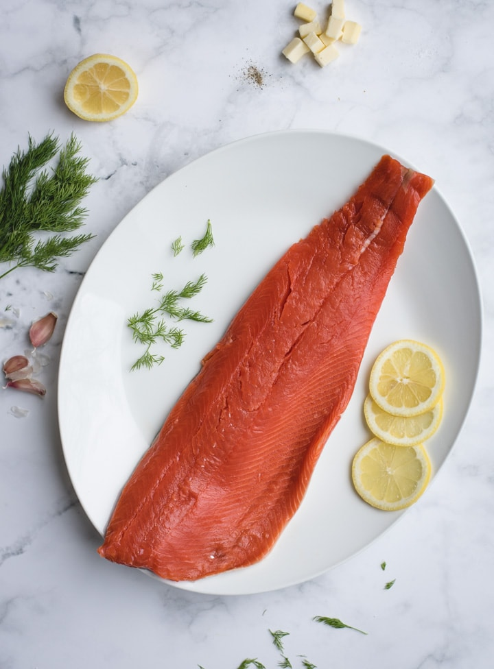 filet of salmon on white background with lemon and dill
