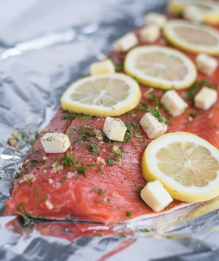 Raw salmon filet topped with butter, lemon, and dill on foil
