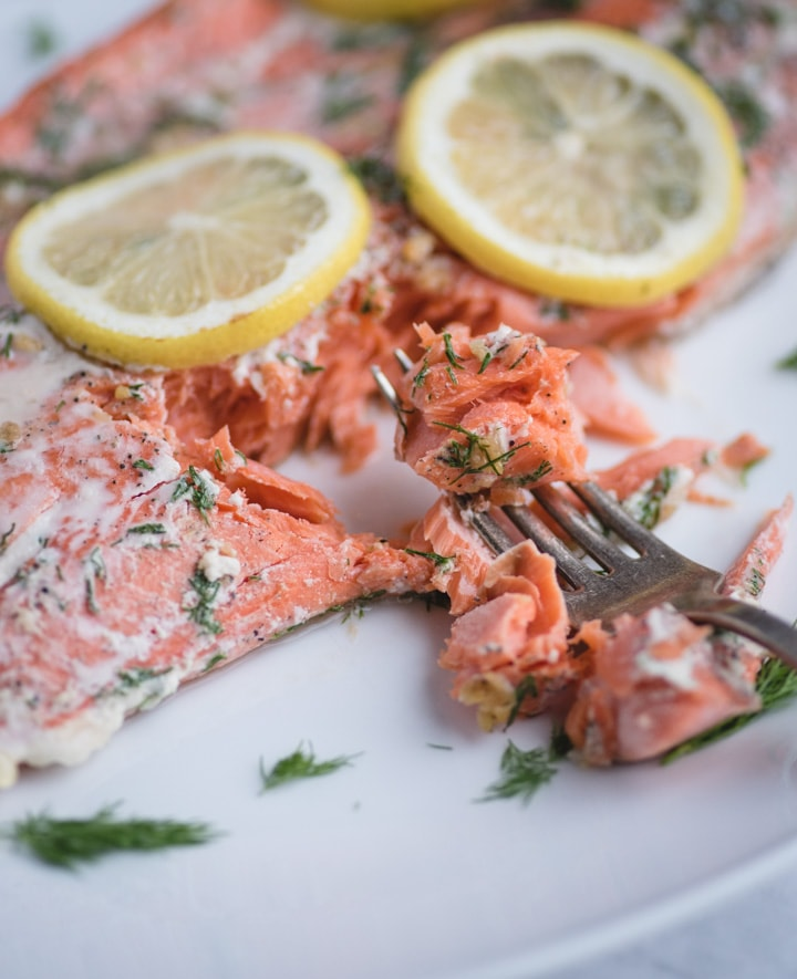 Close up picture of fork with flaked salmon with lemon and dill
