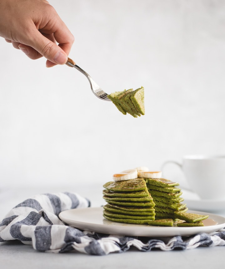 hand holding bite of green pancakes over plate of pancakes