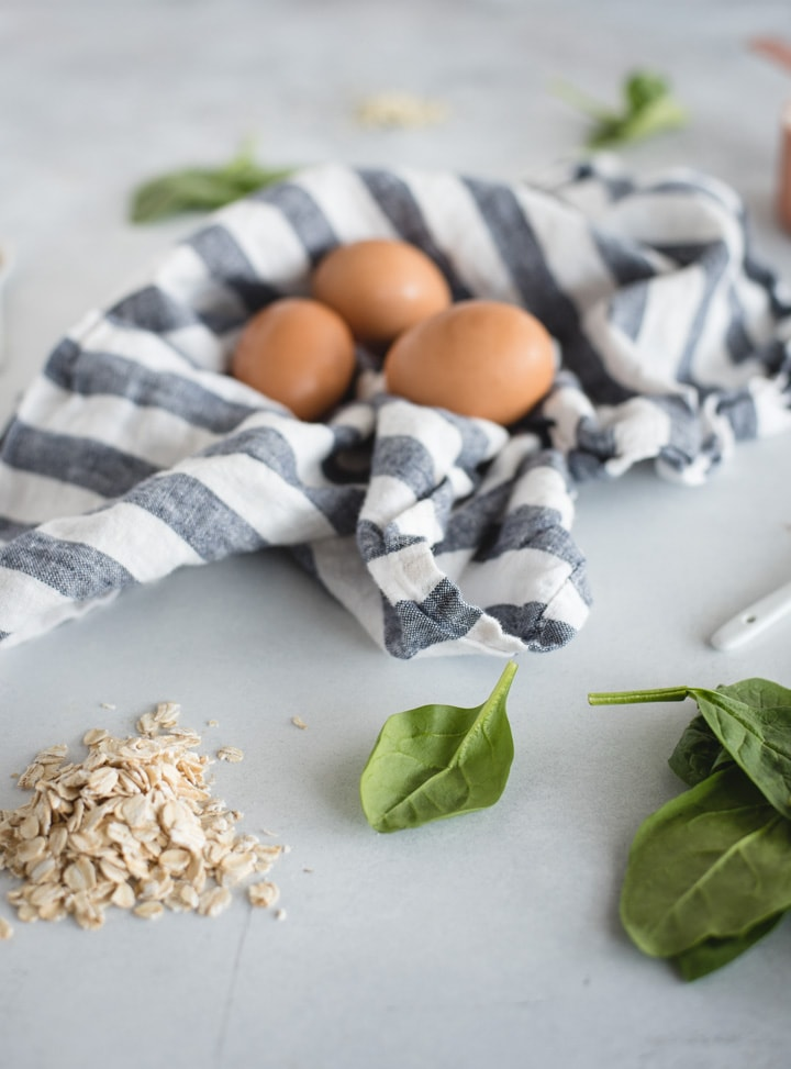 ingredients for spinach pancakes on light background