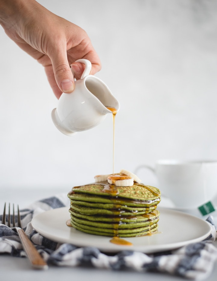 Hand pouring syrup onto a stack of spinach pancakes
