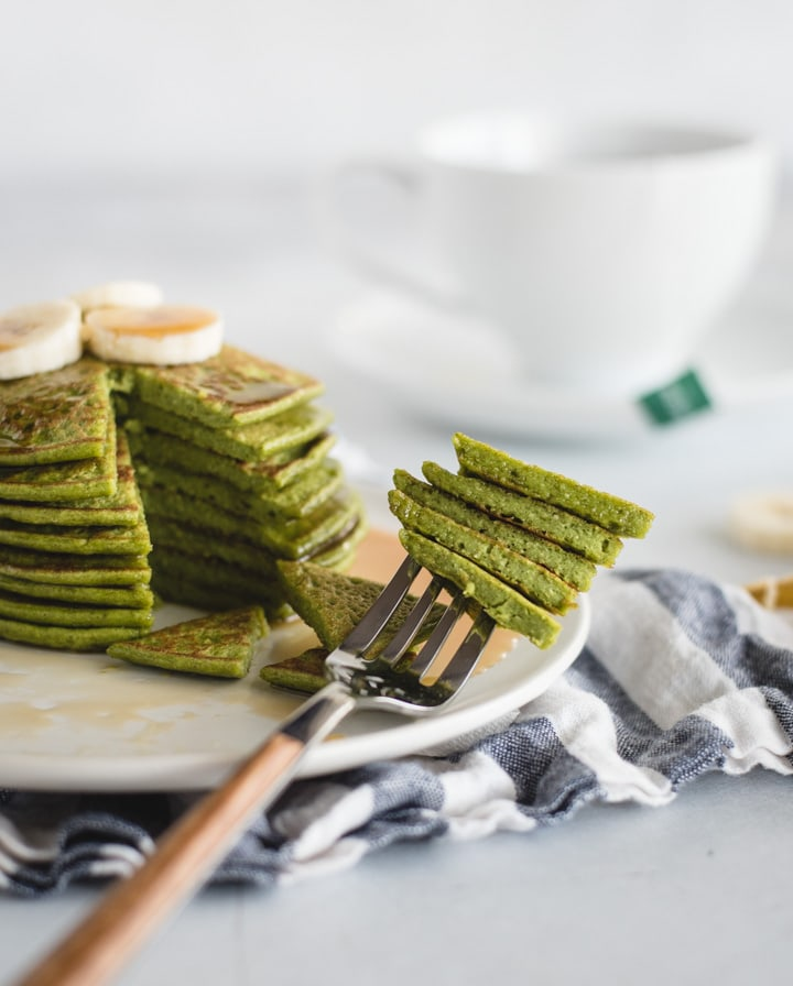 stack of green pancakes with a fork stabbing a bite