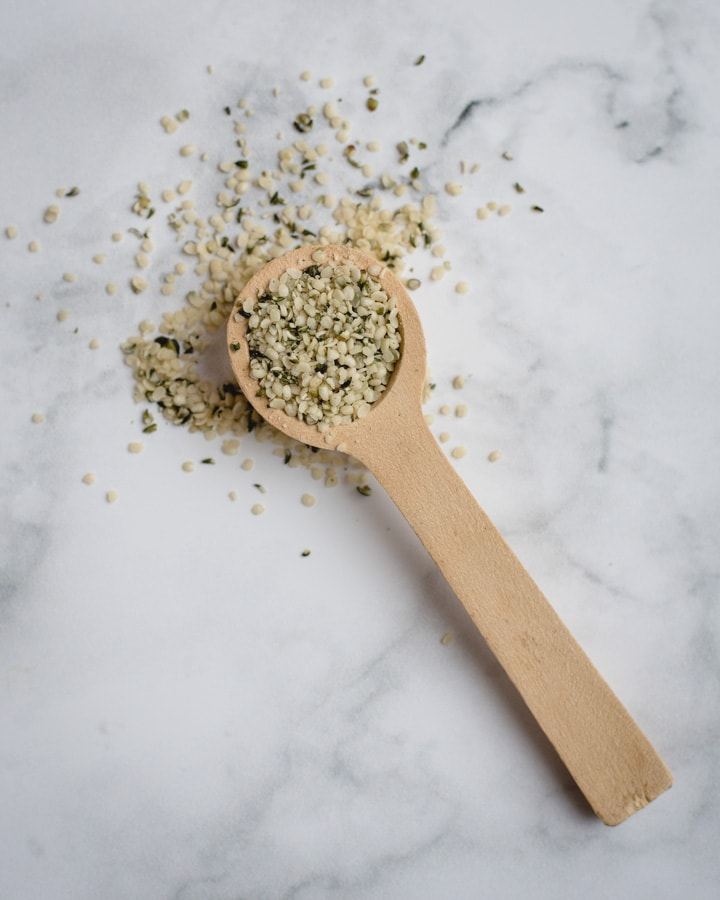 hemp hearts in a wooden spoon on white marble background