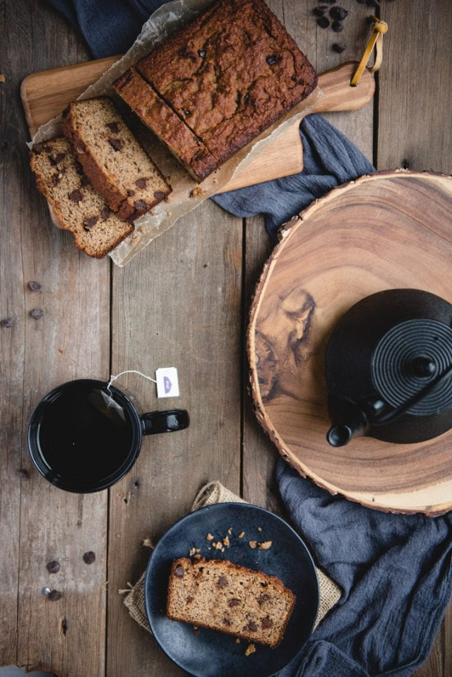 overhead picture of almond flour banana bread loaf with teapot, cup, and plate with slice of bread