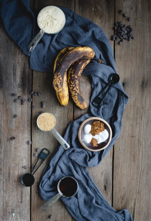 Brown bananas and other banana bread ingredients on a dark wooden background