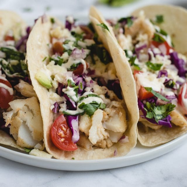 Close up picture of fish tacos on a white plate