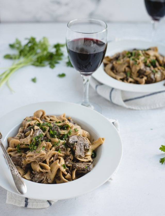 bowls of beef stroganoff with red wine