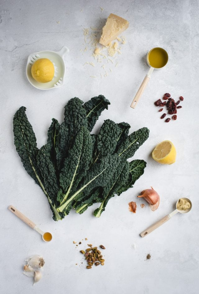 overhead picture of kale, lemon and other ingredients laid out on gray background