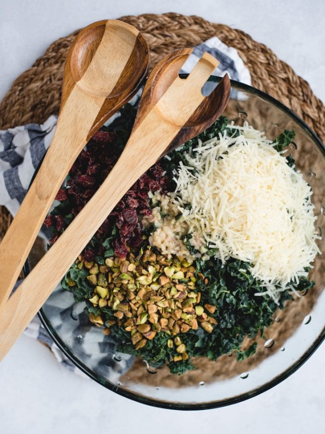 overhead picture of kale salad with parmesan, cranberries, and pistachios on top