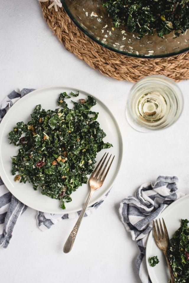 close up picture of white plate with kale salad and white wine