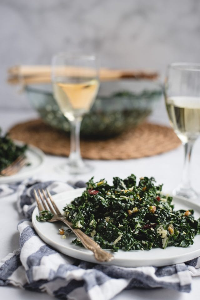 side view picture of kale salad on a plate with wine and big salad bowl in background