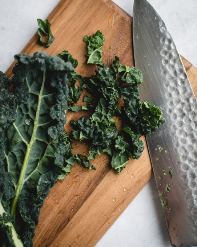 kale leaf next to chopped pieces of kale and knife on cutting board